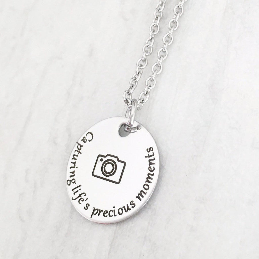 "full view of necklace with is engraved with ""capturing life's most precious moments"""