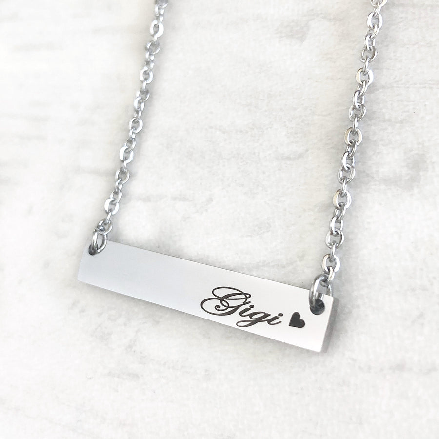"silver horizontial bar necklace with engraved ""gigi"" and small heart shiloutte attached to a stainless steel cable chain with lobster clasp"