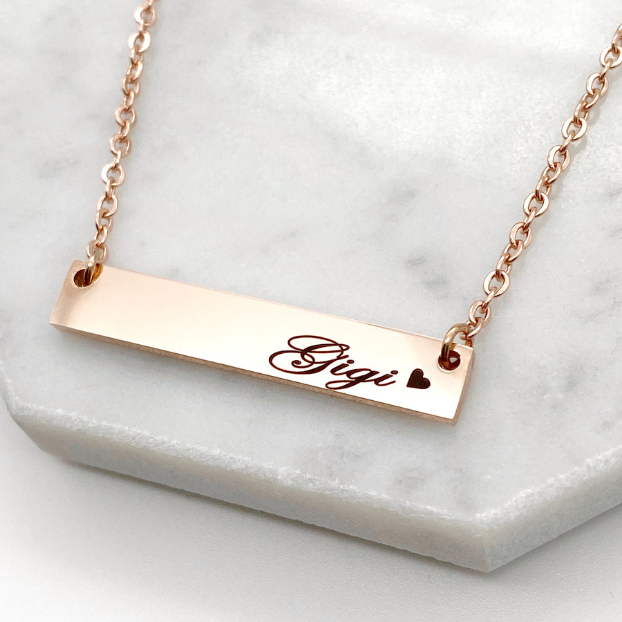 rose gold horizontal rose gold bar necklace engraved wth gigi and a small heart shilouette  attached to a rose gold stainless steel cable chain