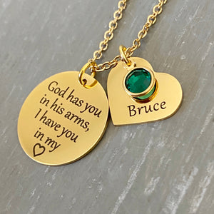 "Yellow Gold Necklace with 3/4 inch round pendant engraved with ""God has you in his arms, I have you in my heart"". Next to the disc is a 3/4 inch heart engraved with Bruce and a green may stone. Pendants are attached to a cable chain"