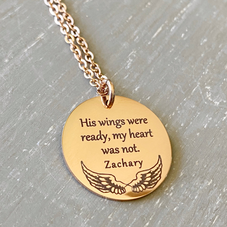 "7/8 inch rose gold pendant necklace engraved with ""Hiswings were ready my heart is not."" with the name ""Zachary"" and angel wing image. The pendant is attached to a cable chain with lobster clasp."