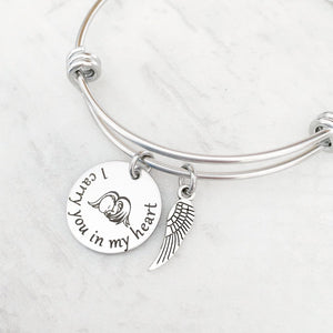 "silver bangle charm bracelet with a 3/4"" round engraved disc with the image of a baby sleeping under angel wings and the verbiage ""I carry you in my heart""  next is an angel wing charm."