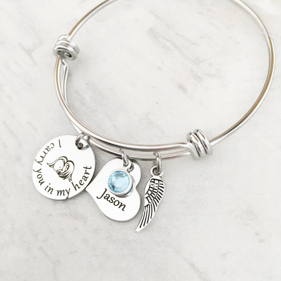 "silver bangle charm bracelet with a 3/4"" round engraved disc with the image of a baby sleeping under angel wings and the verbiage ""I carry you in my heart"" next to it is a 3/4"" heart engraved with the name ""Jason"" and. a blue march birthstone. Last is an angel wing charm."