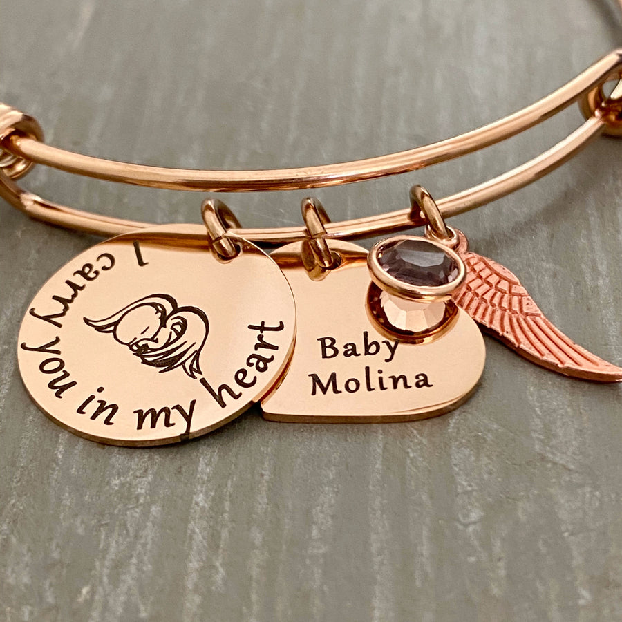"rose gold bangle charm bracelet with a 3/4"" round engraved disc with the image of a baby sleeping under angel wings and the verbiage ""I carry you in my heart"" next to it is a 3/4"" heart engraved with the name ""Baby Molina"" and. a diamond april birthstone. Last is an angel wing charm."