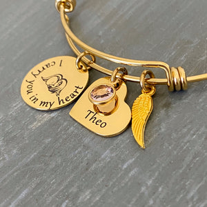 "yellow gold bangle charm bracelet with a 3/4"" round engraved disc with the image of a baby sleeping under angel wings and the verbiage ""I carry you in my heart"" next to it is a 3/4"" heart engraved with the name ""Theor"" and a purple June birthstone. Last is an angel wing charm."