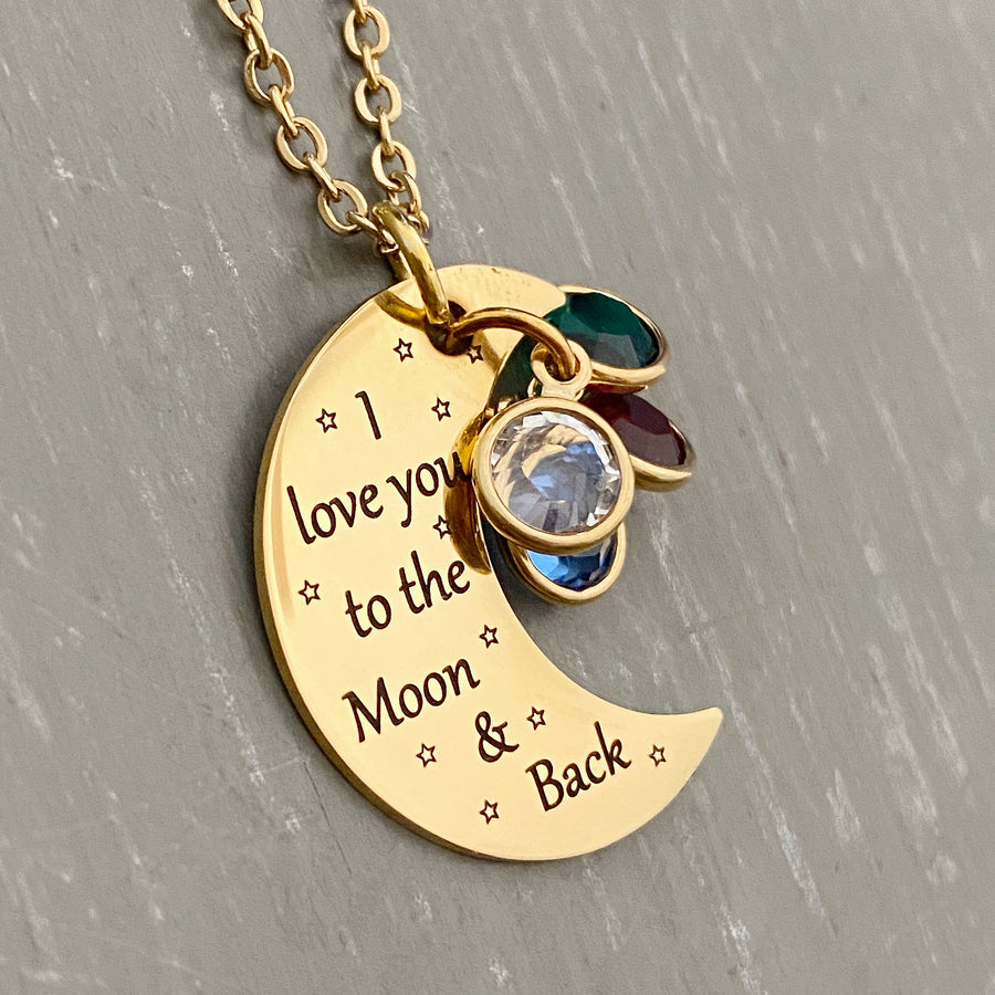 "yellow gold half moon charm with black engrave tiny stars and the saying ""I love you to the moon & back"". attached to the moon are a april, june, may, and february birthstone. The moon birthstone necklace hangs from a yellow gold cable chain."