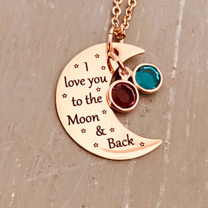 "rose gold half moon charm with black engrave tiny stars and the saying ""I love you to the moon & back"". attached to the moon are a december and february birthstone. The moon birthstone necklace hangs from a rose gold cable chain."