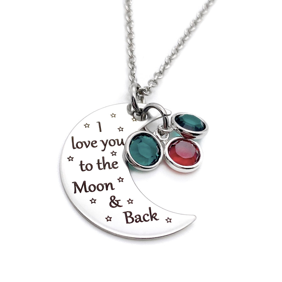 "silver half moon charm with black engrave tiny stars and the saying ""I love you to the moon & back"". attached to the moon are two may and february birthstone. The moon birthstone necklace hangs from a silver cable chain."
