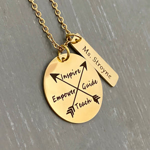 "A 1 inch plated yellow gold disc engraved with a cross arrow design and the words Inspire, Empower, Guide, and Teach. Next to the disc is a 1.2"" rectangle with the teachers name ""Ms. Stroyne"". Charms are attached to a yellow gold cable chain"