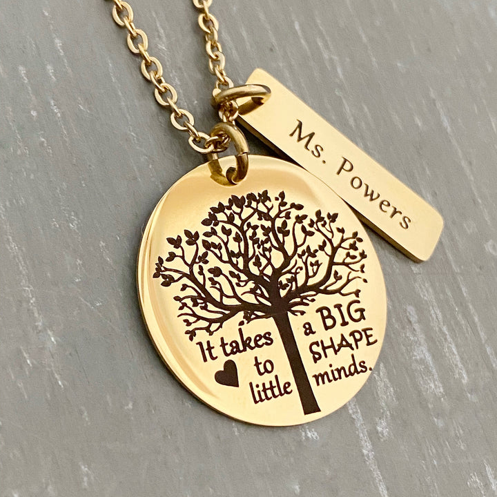 "A 1-inch round stainless steel plated yellow gold disc engraved with a tree of life symbol and the verbiage ""it takes a BIG heart to shape little minds."" Next to the disc is attached a 1-inch rectangle tag engraved with the name ""Ms Powers"". Both Charms are attached to a yellow gold cable chain"