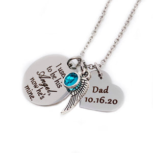 "silver stainless steel 7/8"" round disc engraved with ""I used to be his Angel, now he's mine"", an angel wing charm, a december blue birthstone, a 3/4"" engraved heart with ""Dad and death date ""10.16.20"". all charms are attached to a silver stainless steel cable chain."