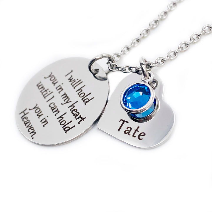 "One 1-inch silver stainless steel disc engraved with ""I will hold you in my heart until I can hold you in Heaven"" Along side is a 3/4"" silver heart engraved with ""Tate"" and a september blue birthstone. Both pendants are attached to a stainless steel cable chain with lobster clasp."