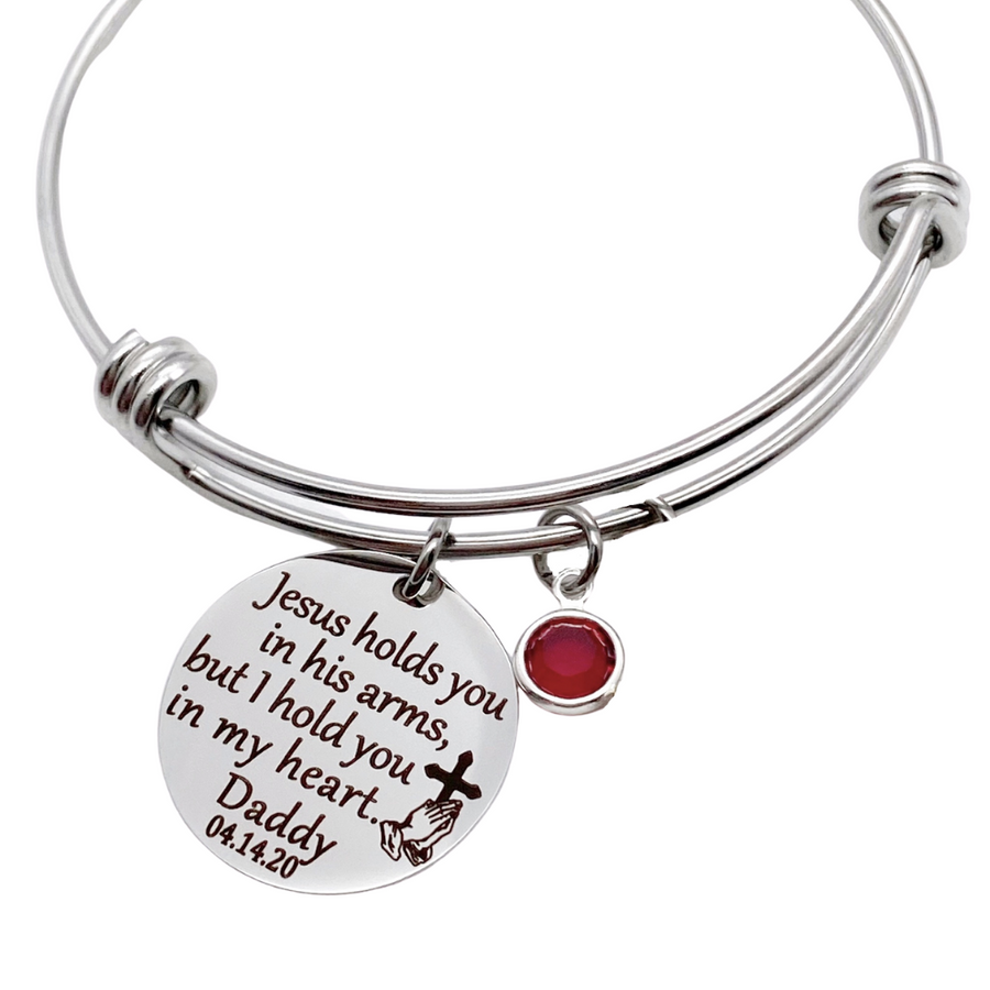 "Silver bangle charm bracelet with 7/8"" engraved disc with the verbiage ""jesus holds you in his arms, but i hold you in my heart."" with the name ""mom"" and date ""7.30.12"" as well as the image of jesus playing hands holding a cross. Next to the disc is a red january crystal stone"