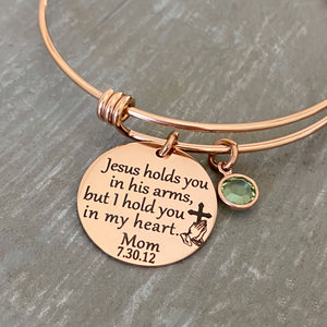 "Rose gold bangle charm bracelet with 7/8"" engraved disc with the verbiage ""jesus holds you in his arms, but i hold you in my heart."" with the name ""mom"" and date ""7.30.12"" as well as the image of jesus playing hands holding a cross. Next to the disc is a august crystal stone"