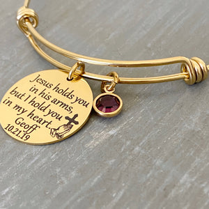 "yellow gold bangle charm bracelet with 7/8"" engraved disc with the verbiage ""jesus holds you in his arms, but i hold you in my heart."" with the name ""mom"" and date ""7.30.12"" as well as the image of jesus playing hands holding a cross. Next to the disc is a purple february stone"