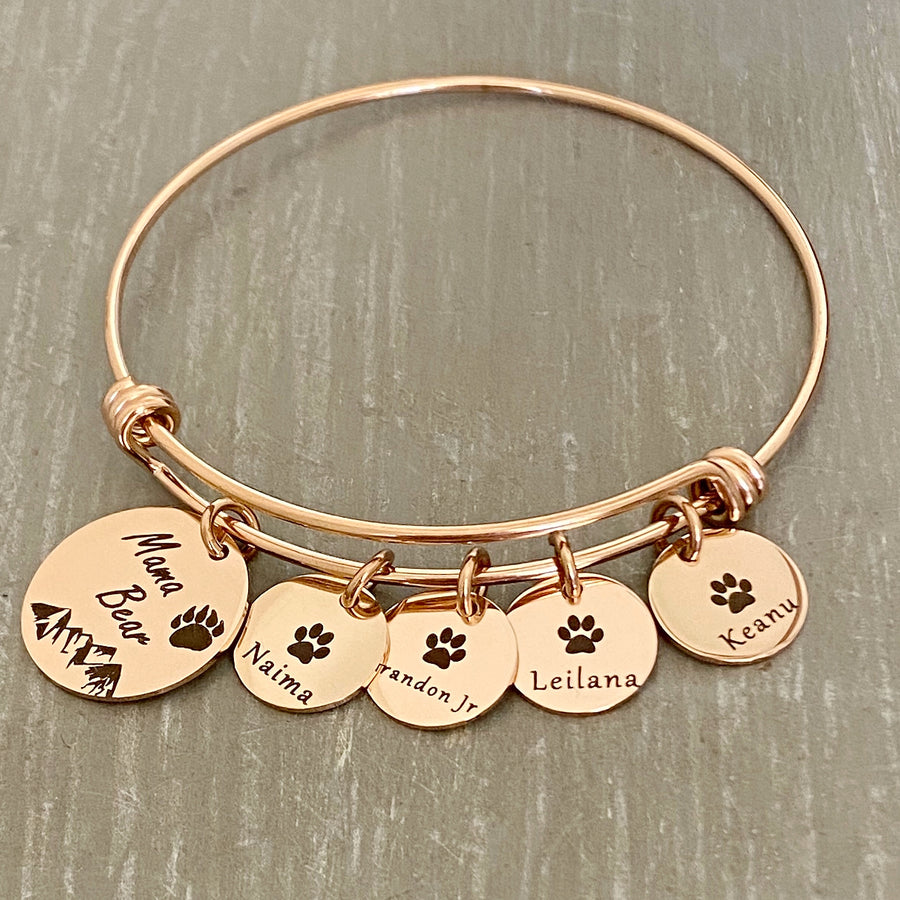 "Rose Gold Bangle adjustable charm bracelet with a 3/4"" engraved disc with a bear paw print, mountain range scene and verbiage ""Mama Bear"" along with three 1/2"" name tags engraved with a cub paw print and the names Naima, Brandon Jr, Leilana, Keanu"