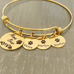 "Yellow Gold Bangle adjustable charm bracelet with a 3/4"" engraved disc with a bear paw print, mountain range scene and verbiage ""Mama Bear"" along with three 1/2"" name tags engraved with a cub paw print and the names Gavyn, Harlyn, Scotlyn"