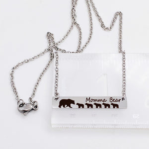 "silver engraved bar necklace with 5 bear cubs and a mom bear. engraved with ""momma Bear"" and attached to a silver stainless steel cable chain. necklace on ruler to show bar is 1.5 inches wide"