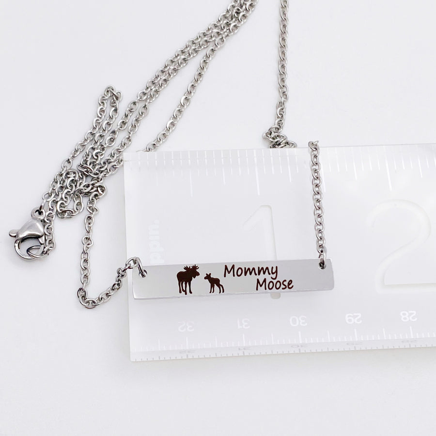 Silver Engraved Mommy Moose Bar Necklace with black engraved mom moose and baby fawn showing on ruler 1.5 inches wide with stainless steel cable chain
