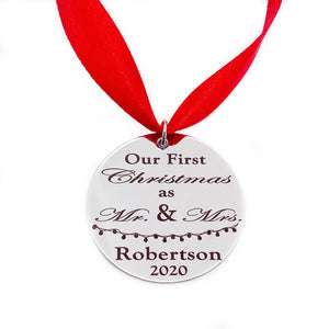 "1.5mm silver stainless steel engraved with ""Our First Christmas as Mr. & Mrs."" with last name robertson and the wedding year 2020. Attached to a red ribbon"