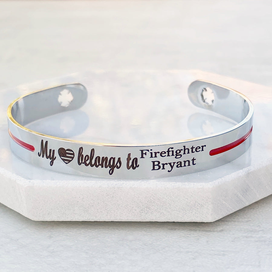 front view of Silver stainless steel cuff bracelet with maltese cross fireman cutout symbol with engraved my american flag heart shape belongs to firefighter bryant