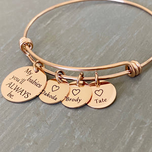 "Rose gold bangle charm bracelet with a 3/4"" disc engraved with ""my babies you'll always be."" and a 1/2"" engraved disc with an open heart and the name Dakoda, a second charm disc with the name Brody, and a third name disc with the name tate."