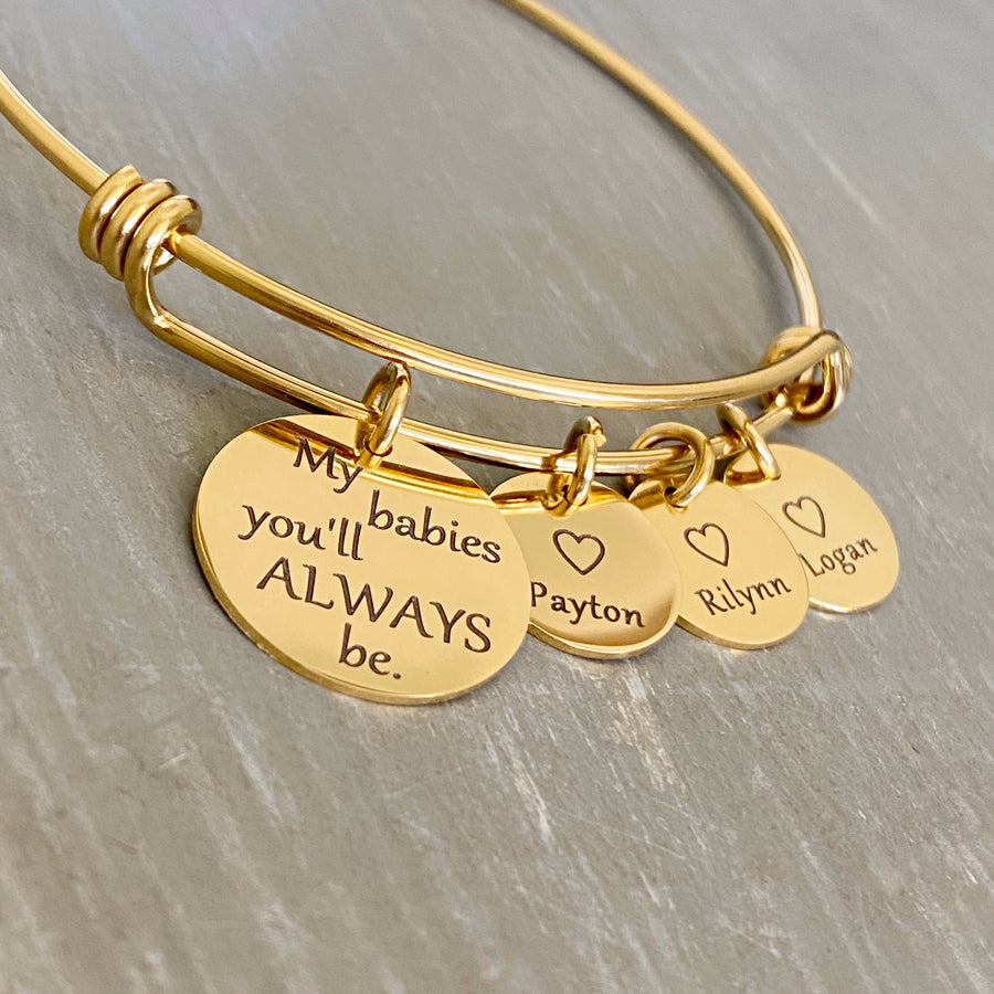 "Yellow gold bangle charm bracelet with a 3/4"" disc engraved with ""my babies you'll always be."" and a 1/2"" engraved disc with an open heart and the name Payton, a second charm disc with the name Rilynn, and a third name disc with the name Logan."