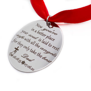 "1.5 inch silver disc engraved with ""now you're in a better place your soul is laid to rest safe with all the angels for they only take the best. Dad 08.08.35 to 7.6.20"" hung by a red ribbon"