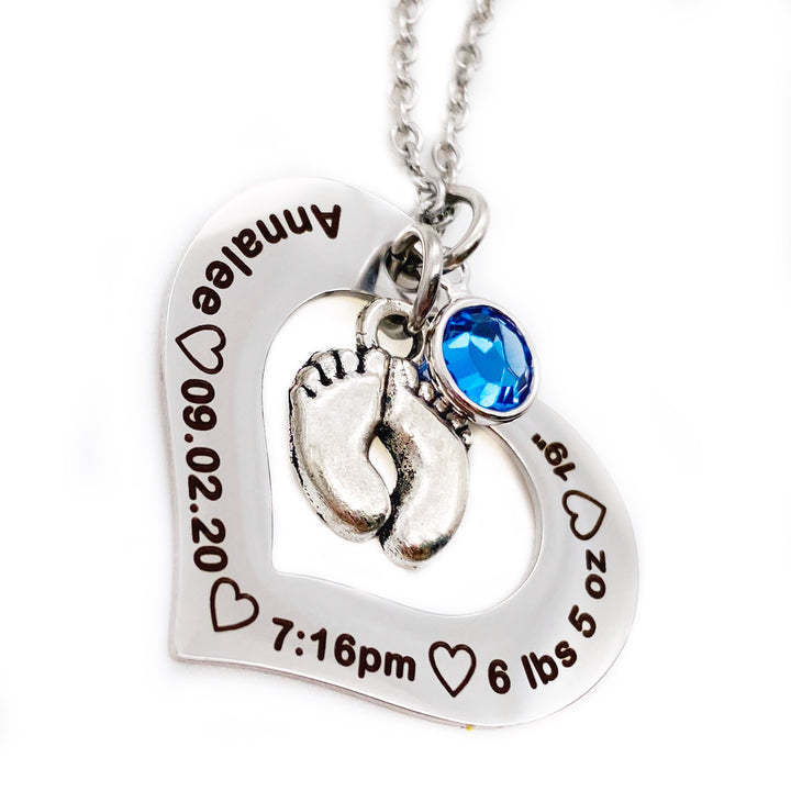 Silver Stainless Steel Open heart pendant attached to a silver cable chain. Baby feet charm and september birthstone attached. Black engraving around the heart charm with the name annalee, birthdate 09.20.20, time of birth 7:16pm, weight 6 lbs 5 oz, and length of 19""