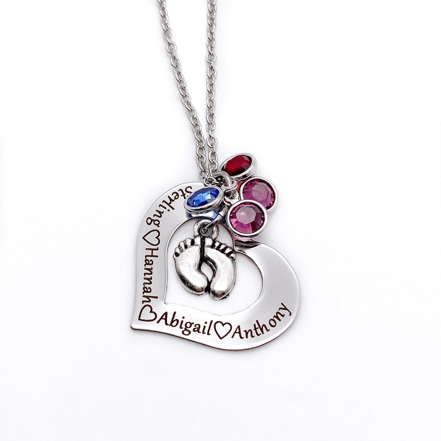 silver open heart necklace engraved with children's names and birthstones. a feet charm hangs in the center of the heart and birthstones
