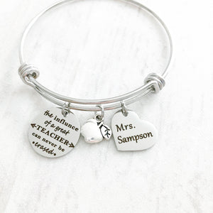 "silver teacher bangle charm bracelet with engraved ""the influence of a great teacher can never be erased"" an apple charm and a 3/4"" heart engraved with teachers name ""mrs sampson"""""