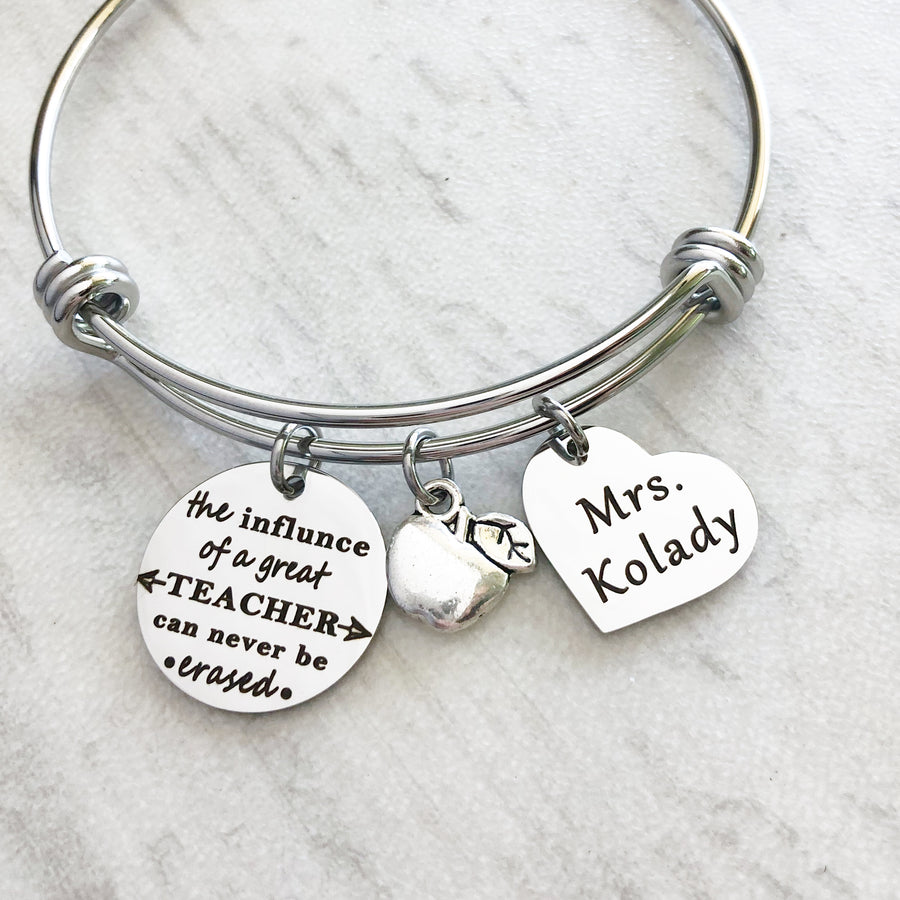 "silver teacher bangle charm bracelet with engraved ""the influence of a great teacher can never be erased"" an apple charm and a 3/4"" heart engraved with teachers name ""mrs kolady"""""