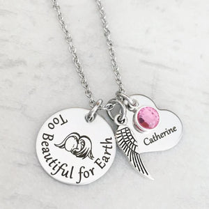 silver round disc engraved with too beautiful for earth and an image of a baby with angel wings, an angel wing, a heart engraved with the name Catherine and a pink October stone. Pendant charms are attached to a silver cable chain.