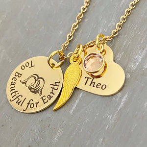 Yellow Gold round disc engraved with too beautiful for earth and an image of a baby with angel wings, an angel wing, a heart engraved with the name Theo and a clear april stone. Pendant charms are attached to a yellow gold cable chain.