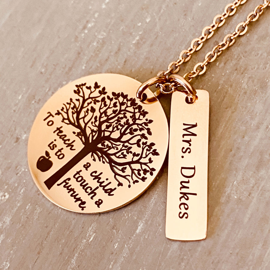 "A 1 inch round stainless steel plated rose gold disc engraved with a tree of life symbol and the verbiage ""To teach a child is to touch a future."" Next to the disc is a 1.2"" rectangle engraved with ""Mrs. Dukes"". The charms are attached to a rose gold cable chain."