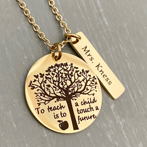 "A 1 inch round stainless steel plated yellow gold disc engraved with a tree of life symbol and the verbiage ""To teach a child is to touch a future."" Next to the disc is a 1.2"" rectangle engraved with ""Mrs. Kness"". The charms are attached to a yellow gold cable chain."