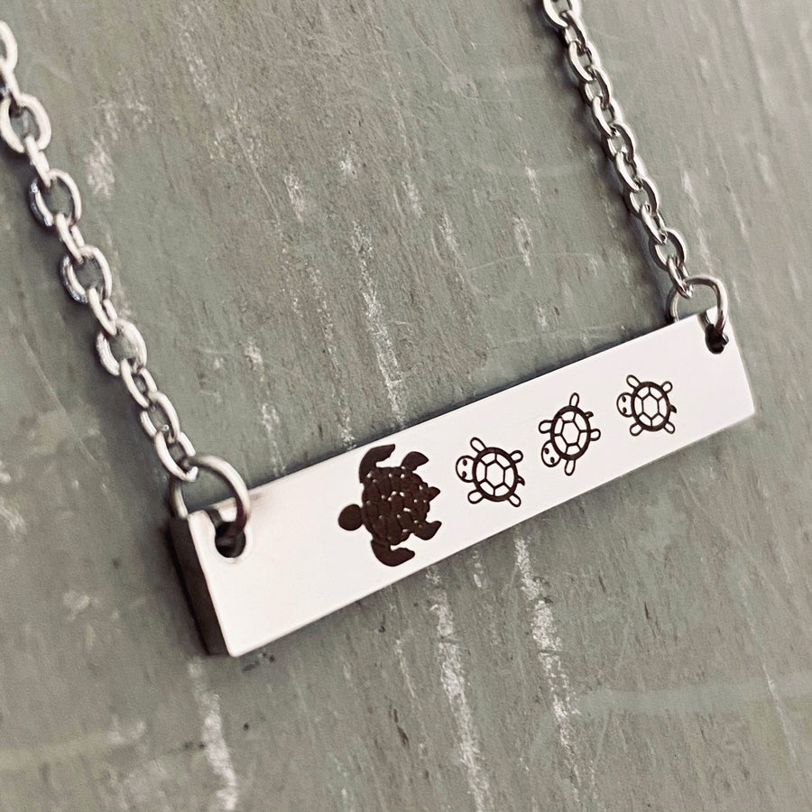 Left side view of a Silver horizontal bar necklace engraved with one mom turtle and 3 baby turtles. The bar is attached to a silver stainless steel cable chain