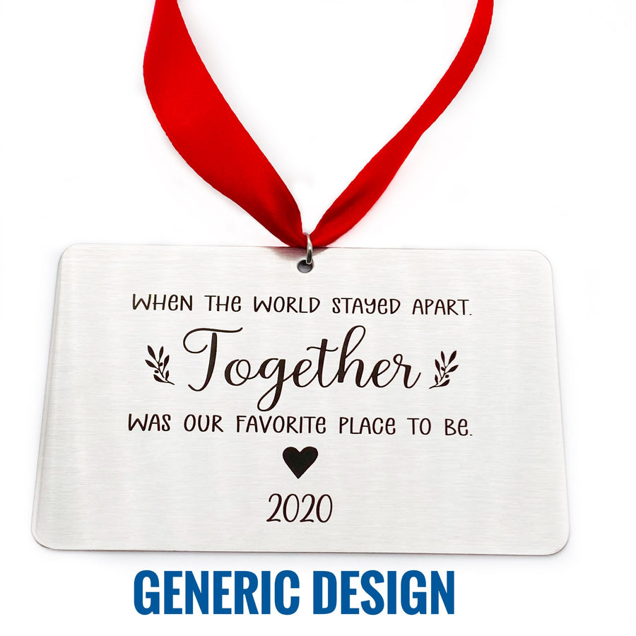 "rectangle silver stainless steel christmas tree ornament engraved with ""When the world stayed apart. Together was our favorite place to be."" underneath the saying is A solid heart image and underneath the heart is the year ""2020"" attached to a red ribbon for tree hanging."
