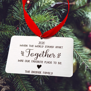 "rectangle silver stainless steel christmas tree ornament engraved with ""2020 When the world stayed apart. Together was our favorite place to be."" A solid heart image and underneath ""The Snyder Family"". attached to a red ribbon for tree hanging."