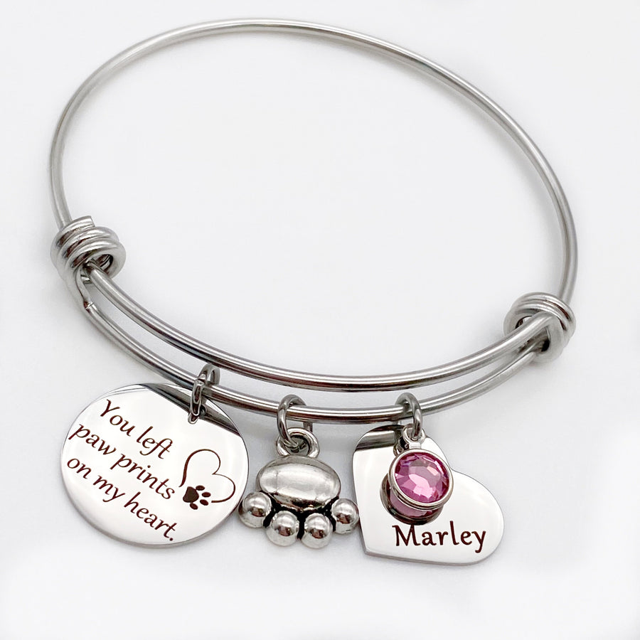 "silver bangle charm bracelet with engraved disc ""you et paw prints on my heart"" a dog paw charm and an engraved heart name tag with dog's birthstone"