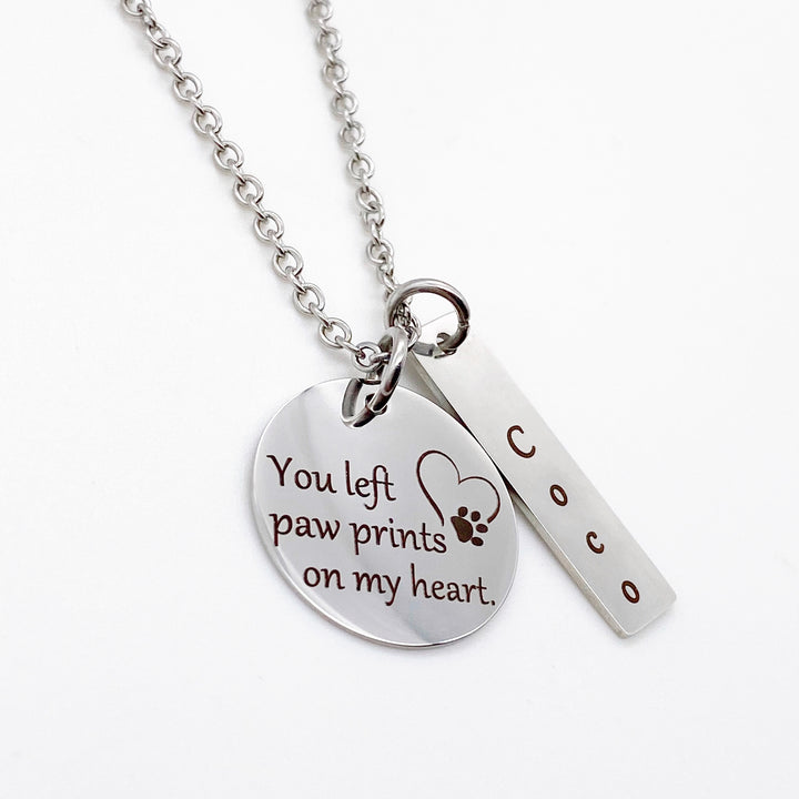 "silver 3/4 inch pendant engraved with ""you left paw prints on my heart"" with an image of a heart and paw print. Next to it is a rectangle tag personalized with the name Coco. Pendants are attached to a cable chain."