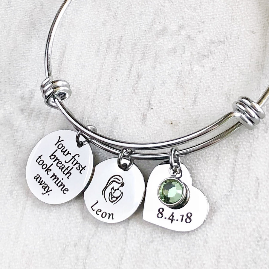 "Silver triple loop wire bracelet with a round 3/4 inch engraved with ""your first breath took mine away"", a 5/8 inch round disc with engraved name ""leon"" and an image of a mom holding a baby, a 3/4 inch heart engraved with the birthday date ""8.4.18"", and a august birthstone."