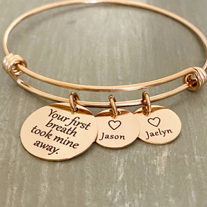"stainless steel rose gold bangle charm bracelet with a 3/4 inch disc engraved with ""your first breath took mine away"". 1/2 inch name discs with open heart image above the engraved name."