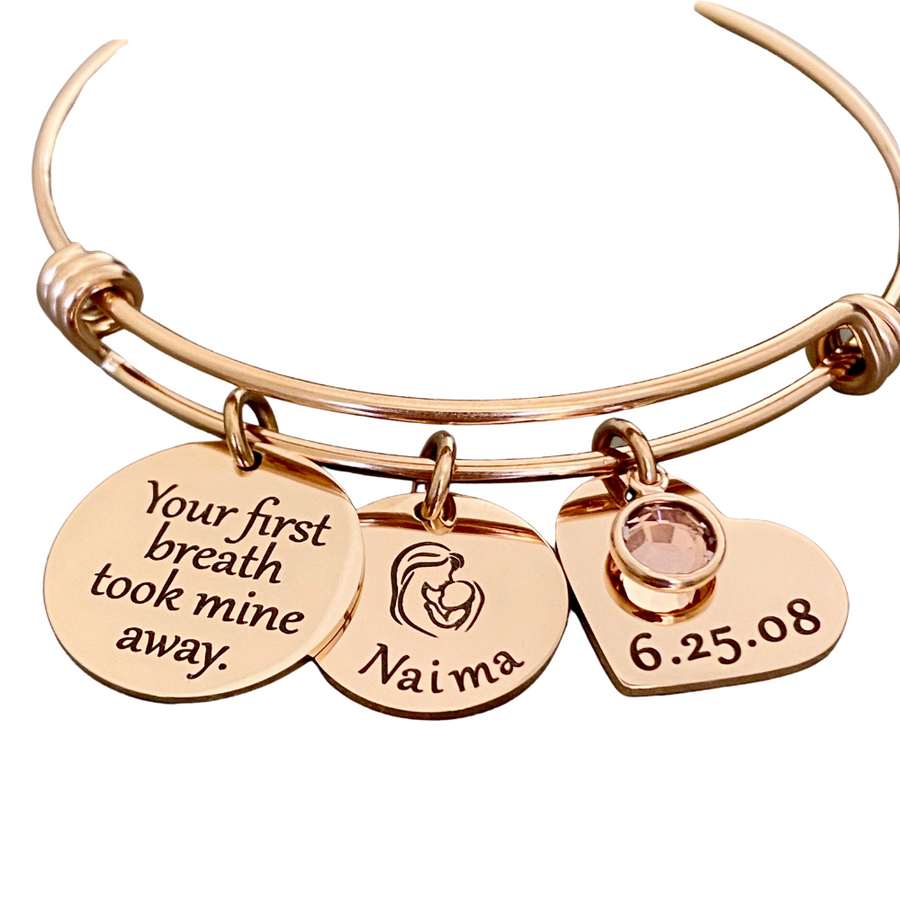 "rose gold triple loop wire bracelet with a round 3/4 inch engraved with ""your first breath took mine away"", a 5/8 inch round disc with engraved name ""Naima"" with an image of a mom holding a baby, and a 3/4 inch heart engraved with the birthday date ""6.25.08"", and a june birthstone."