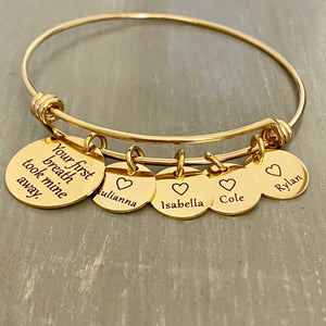 "stainless steel yellow gold bangle charm bracelet with a 3/4 inch disc engraved with ""your first breath took mine away"". 1/2 inch name discs with open heart image above the engraved name."