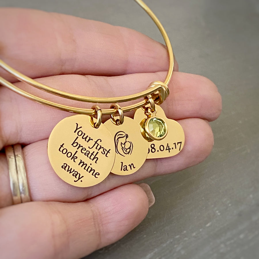 "Woman holding a yellow gold triple loop wire bracelet with a round 3/4 inch engraved with ""your first breath took mine away"", a 5/8 inch round disc with engraved name ""Ian"" with an image of a mom holding a baby, and a 3/4 inch heart engraved with the birthday date ""8.04.17"", and an august birthstone."
