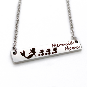 "engraved 1.2-inch by .25 inch bar necklace in silver gold or rose gold and engraved with a mom mermaid image and your choice of mermaid babies. Engraved with the verbiage ""mermaid mama"""