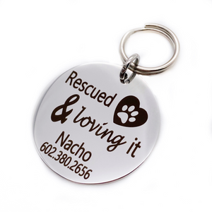 "Silver stainless steel dog collar id tag with black engraving ""Rescued & Loving it"" with a picture of a heart with a dog paw inside, pets name and telephone number"