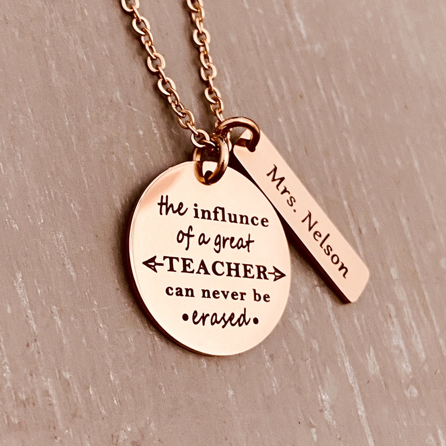 "A 1 inch round stainless steel plated rose gold disc engraved with the verbiage ""The influence of a great teacher can never be erased."" Next to the disc is a 1.2"" rectangle engraved with ""Mrs. Nelson"". The charms are attached to a rose gold cable chain."