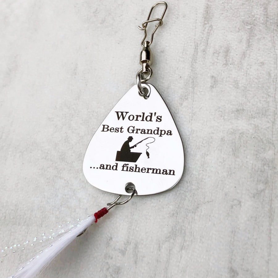 worlds best grandpa and fisherman silver fishing lure with man in boat fishing and white feather